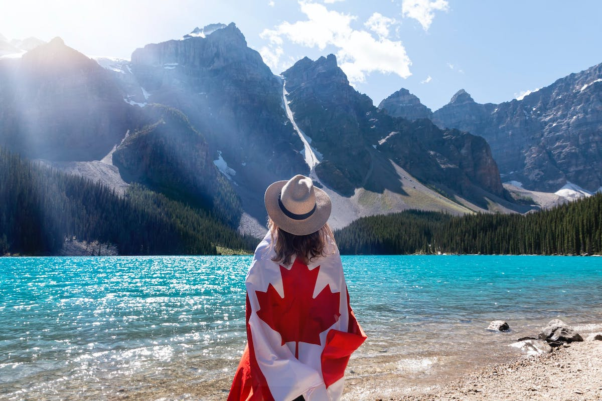 a woman in canada standing in front of a lake with a canada flag wrapped around her
